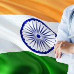 Indian Doctor standing with stethoscope on India flag background. National healthcare system concept, medical theme. Image credit: Sezer özger / 123rf. violence against doctors concept.