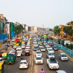 DELHI, INDIA - JULY 5, 2016: Heavy road traffic in the city center of Delhi, India. Buses and construction nearby the road. Various shops, cafes, restaurants Image credit: madrugadaverde / 123rf. Elimination of leaded fuel concept.